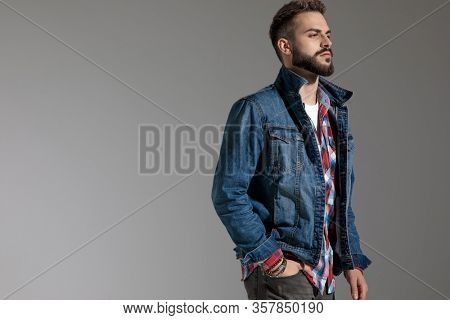 side view of a sexy casual man wearing denim jacket standing with one hand in pocket and looking away with tough attitude on gray studio background
