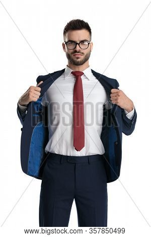 attractive businessman wearing glasses standing and pulling back his jacket tough on white studio background