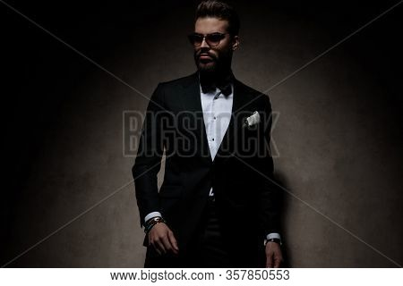 handsome businessman wearing sunglasses standing and striking a pose with tough attitude on dark studio background