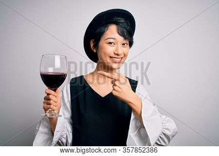 Young beautiful asian sommelier girl drinking glass of red wine over isolated white background very happy pointing with hand and finger