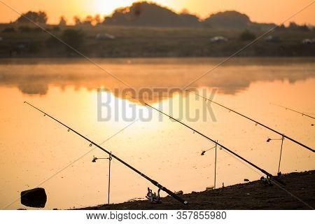 Freshwater Fishing With Fishing Rods On The Shore Of The Pond, Lake.