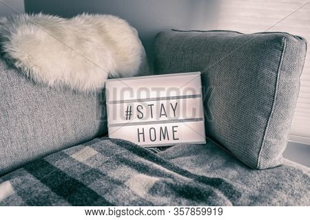 Coronavirus home lightbox sign with hashtag message #STAYHOME glowing on home sofa with cozy lambswool fur, blanket. COVID-19 text to promote self isolation staying at home.