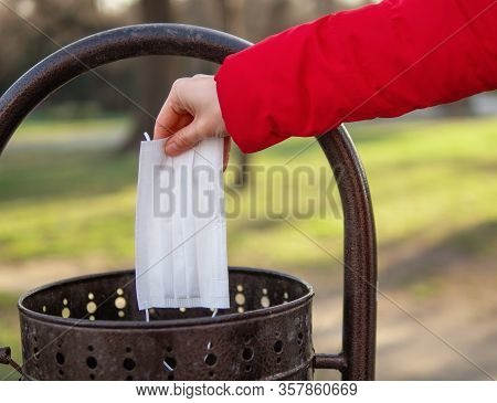 Hand Throwing A Surgical Mask Into The Bin In The Park