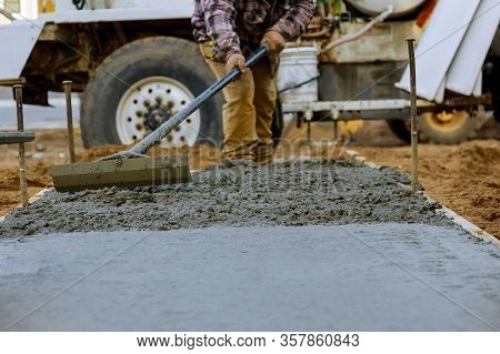 Construction Worker Pour Cement For Sidewalk In Concrete Works With Mixer Truck With Wheelbarrow At