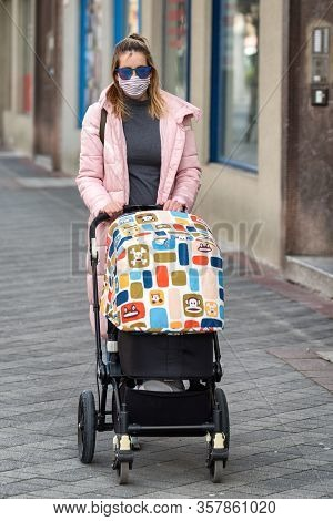 Ruzomberok, Slovakia - March 26: Woman In Face Mask Pushing A Stroller In The Cityon March 26, 2020