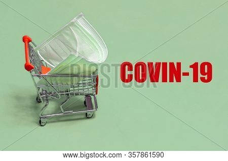 Protective Medical Masks In Small Shopping Trolley With The Text Covin-19 On Green Background. Panic