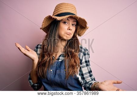 Young beautiful brunette farmer woman wearing apron and hat over pink background clueless and confused expression with arms and hands raised. Doubt concept.