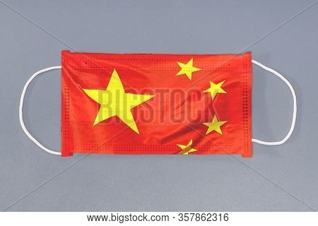 Isolated Medical Mask With Flag Of China On Gray Background. Closeup Protective Masks Textile Filter