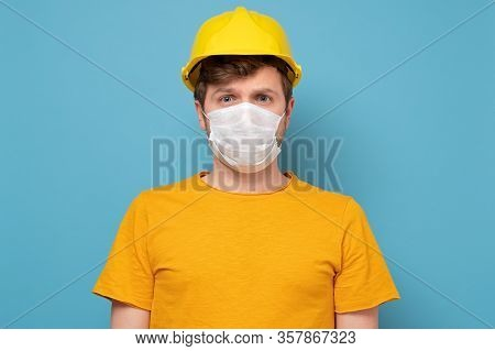 Workman Wearing A Yellow Hard Hat And Medical Mask During Quarantine