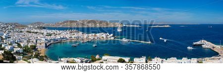 Panorama of Mykonos town Greek tourist holiday vacation destination with famous windmills, and port with boats and yachts. Mykonos, Cyclades islands, Greece
