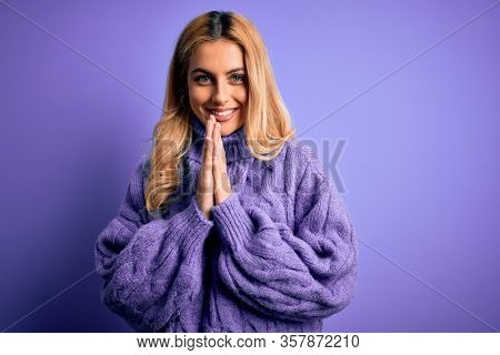 Young beautiful blonde woman wearing casual turtleneck sweater over purple background praying with hands together asking for forgiveness smiling confident.