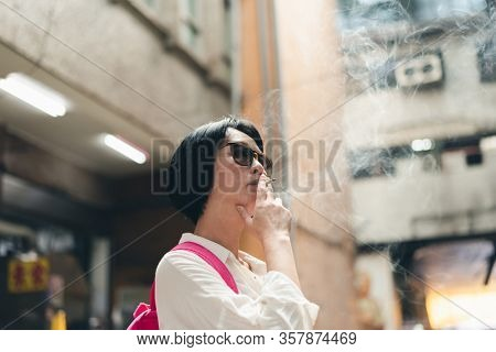 Asian woman traveling and smoking in the traditional marketplace at Taiwan