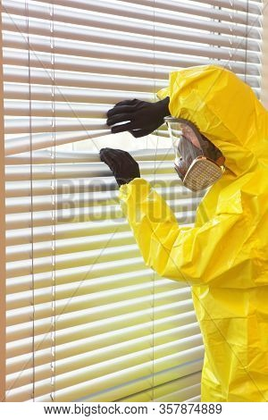 Quarantine - man in professional mask and uniform looking through window blinds