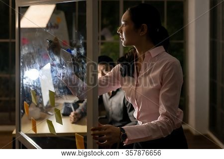 Young adult asian businessman and businesswoman meeting using whiteboard late at night in their office with desktop computer. Using as hard working and working late concept.