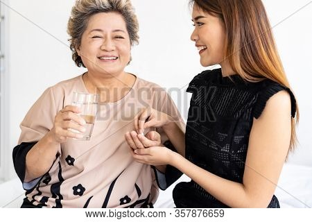 Close up of Caregiver woman helping old elderly woman taking medicine pill on the bed and check up her at home.
