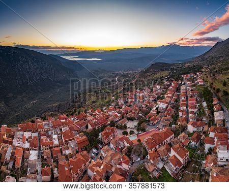 Aerial View Of Delphi, Greece, The Gulf Of Corinth, Orange Color Of Clouds, Mountainside With Layere
