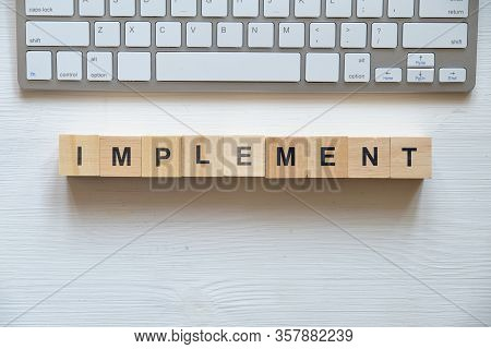 Modern Business Buzzword - Implement. Top View On Wooden Table With Blocks. Top View. Close Up.