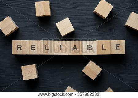Modern Business Buzzword - Reliable. Top View On Wooden Table With Blocks. Top View. Close Up.