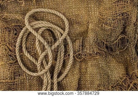 Hemp rope on burlap. Close-up of a natural rope and fabric. Calm nice background.