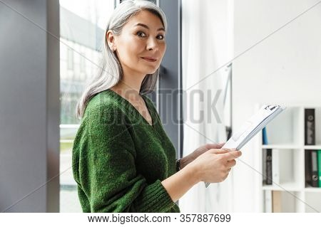Attractive smiling mature woman with long gray hair standing at the window indoors, holding clipboard
