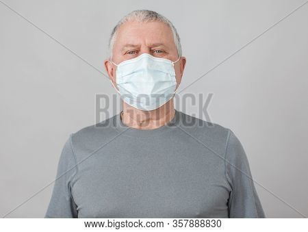 Senior in medical mask isolated on gray background. Studio portrait of adult man looking at camera Flu epidemic, dust allergy, protection against virus. Covid-19, coronavirus pandemic