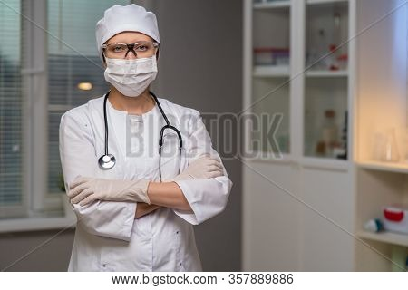 Female Doctor In Laboratory Office On Background Of Test Tubes And Medical Equipment On Background Of Test Tubes And Medical Equipment Masked Gloves And Glasses