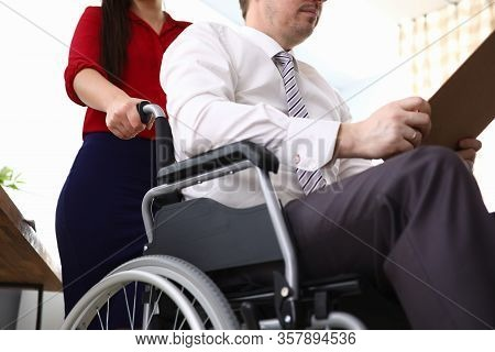 Close-up Of Woman Co-worker Accompany Man In Disabled Carriage. Employee Reading Important Papers. B