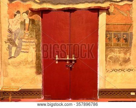 Old Red Door And Pu Man Ya Man Mural Wall Painting Ancient Interior At Phumin Temple, Nan Province,