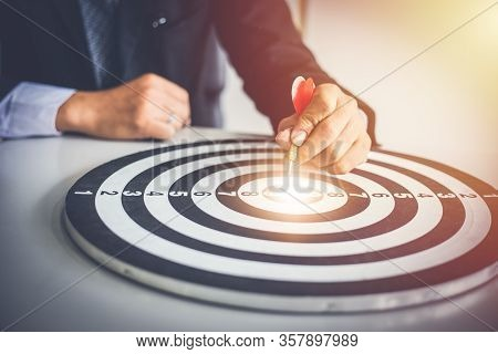 Business Man Holding Dart Hits Bullseye Is A Target And Goal Of Business Marketing As Concept.