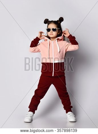 Frolic Curious Kid Girl With Straight Brunette Hair With Buns In Modern Fashion Pink Brown Sportsuit
