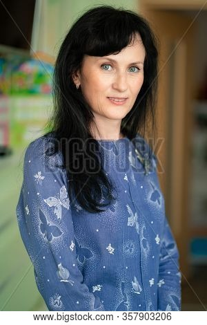 Business Portrait Of An Adult Woman With Dark Hair In A Blouse And Slacks.