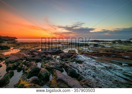Seascape For Background. Beach With Rocks And Stones. Low Tide. Sun And Cloud Reflection In Water. S