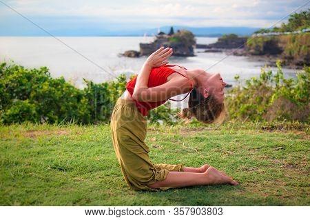 Outdoor Yoga Practice. Young Woman Practicing Ushtrasana, Camel Pose, Kneeling Back Bending Asana. F