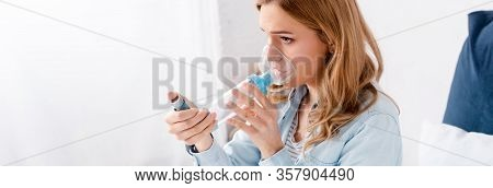 Panoramic Shot Of Asthmatic Woman Using Inhaler With Spacer