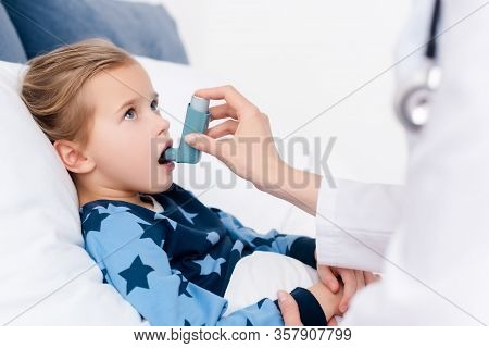 Selective Focus Of Doctor Holding Inhaler Near Asthmatic Child With Opened Mouth