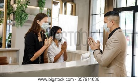 Hotel Guest And Receptionist Wearing Mask To Protect From Conronavirus Covid 19 Having New Practice