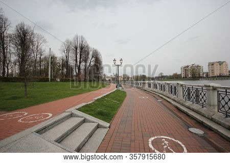 Bike Path And A Footpath On The Citys Stone Embankment. City Park With Green Lawns In Autumn In Kali