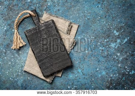 Top View Of Rustic Wooden Cutting Board With Gray Serviette On Blue Concrete Background With Copy Sp