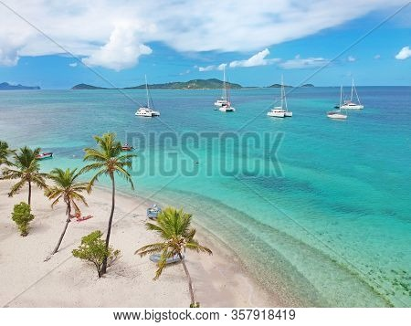 Aerial view of Petit Rameau tropical Caribbean Island beach, sailing catamarans and boats from above