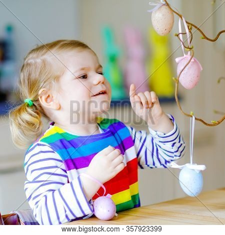 Cute Little Toddler Girl Decorating Tree Bough With Colored Pastel Plastic Eggs. Happy Baby Child Ha