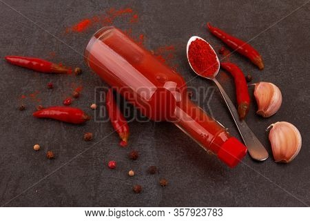 Bottle Of Spicy Red Hot Sauce On Black Background