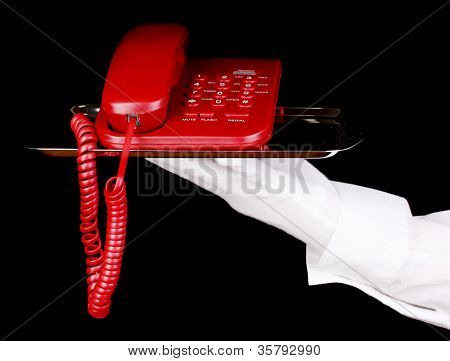 Hand in glove holding silver tray with telephone isolated on black