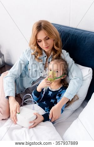 Asthmatic Kid In Respiratory Mask Looking At Camera Near Caring Mother