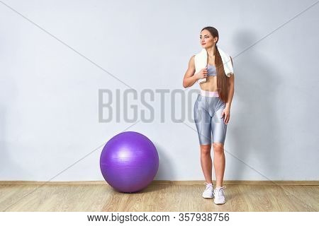 Young Fit Woman Exercising In A Gym. Sports Girl Is Training Cross Fitness With Pilates Balls.