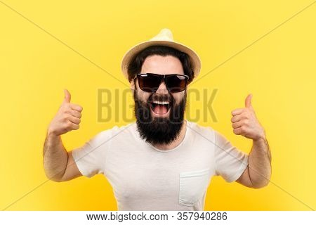 Cheerful Bearded Guy In Sunglasses And A Panama Hat, Man Shows Like On Yellow Background, Concept Of