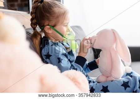 Selective Focus Of Asthmatic Kid Using Respiratory Mask And Playing With Soft Toy