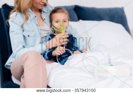 Selective Focus Of Compressor Inhaler Near Asthmatic Kid And Caring Mother
