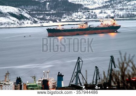 Cargo Ship Of Red Color In The Kola Bay, City Of Murmansk, In Winter, Snowy Water Surface, Long Expo