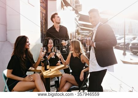 Pretty Girls Sitting In Outdoor Restaurant Beside White Wall And Celebrating Something. Portrait Of