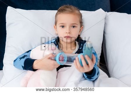 Asthmatic Kid Holding Inhaler With Spacer Near Soft Toy
